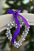 A heart-shaped pearl necklace with a purple ribbon