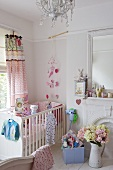 A white cot in a corner of a child's bedroom