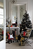 A musical instrument and presents in front of a wall table and a Christmas tree