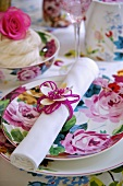 A rolled napkin with a ring and a floral patterned place setting