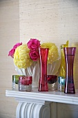 Coloured glass vases and tea lights in front of a bunch of flowers on a mantelpiece