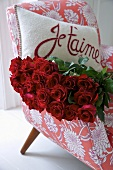 Red roses and a cushion with a love declaration on an armchair