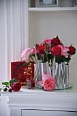 Einzelne Rosen in zylinderförmigen Vasen aus Metall
