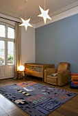 A child's room in a country house with a blue wall and a cot, a leather armchair and a rug