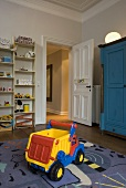 Child's room with a toy on a carpet and open door with a view of a hallway