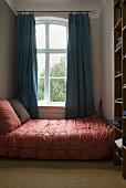 A double bed with a pink plaid cover next to a window with blue curtains