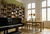 A piano in a living-room-cum-dining-room in front of a window and a balcony door