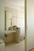 A view through an open sliding door onto a wash basin in a bathroom