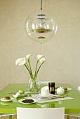 Designer pendant light above a green dining table set for breakfast
