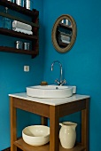 Corner of a room painted blue with a wash stand and washbasin