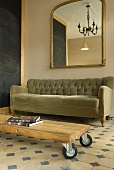 A grey sofa and a wheeled coffee table with a simple wooden top