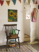 A rustic wooden chair on a striped rug and an open, white-painted door
