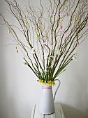 Budding branches and spring flowers with Easter decoration in a white pitcher
