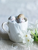 Speckled eggs in a white cup and flowers on a lace tablecloth