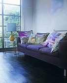 A purple sofa with cushions next to a window