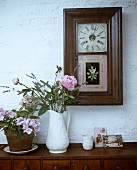 Flowers in a white jug on a wooden cupboard and a framed wall clock