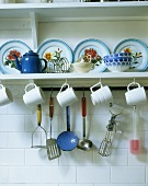 Mugs and kitchen utensils hanging on a plate rack