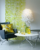 A white table and a black designer swivel chair in front of a green wall covering