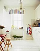 weiße Küche im Landhausstil mit Holzhockern