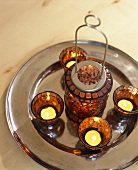 Tea light in a brown glass holders and lantern on a silver platter