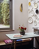 A corner of a kitchen with plates hanging on the wall above a table and a bench