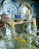 Porcelain candlesticks in front of crockery on a shelf