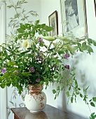 A bunch of flowers in a jug on a wooden shelf