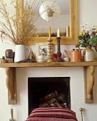 Rustikale Holzablage mit Kerzenleuchtern vor Spiegel über Kamin