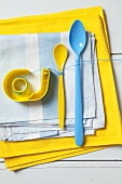 An arrangement of blue and yellow - a sticky tape dispenser and plastic spoons on a pile of tea towels