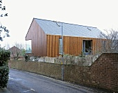Vertical wood panelling on a newly built house with a corner window and a brick wall