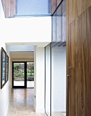 A hallway with a wooden, built-in cupboard and a view into an open room to the terrace door