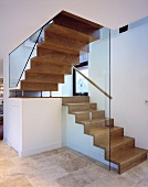 A wooden stairway and glass side walls in an open stairwell
