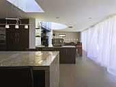 Open-plan living in a newly built house with a curtain in front of the window bank