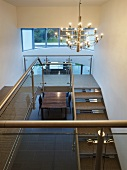 An open stairway with steel steps and a designer pendent lamp