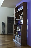 An antique bookshelf in front of a purple wall
