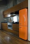 An open-plan kitchen with an orange 1950s style fridge