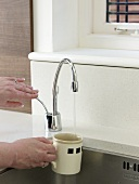 A hand holding a cup under a tap