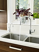 A white work surface with a stainless steel sink