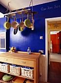 Küchenmöbel mit Schneideblock und Kochgeschirr am Regal hängend vor blauer Wand