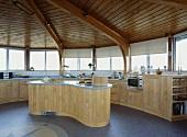 Kreisförmiger Raum mit Holzdecke und offene Küche mit geschwungener Kochinsel