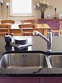 Edelstahlspüle mit Küchenarmatur in Arbeitsplatte aus Granit