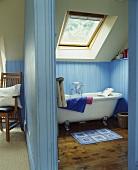 Blick durch offene Tür in blaues holzvertäfeltes Bad mit Dachfenster über freistehender Badewanne im Vintagelook