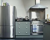 Kühlschrank und Küchenofen aus Edelstahl neben Küchenunterschrank mit grauer Holzfront