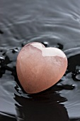 Heart made of rose quartz in a black bowl with water