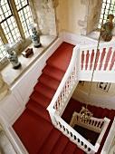 Aufsicht auf eine georgianische Treppe mit rotem Teppich, Sprossenfenstern und Steinrahmen um die Fenster