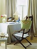 Esszimmer mit Meeresblick mit antikem Klappstuhl, daran hängender grüner Tasche und einem Tisch mit pastellblauer Tischdecke