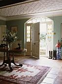 Große Landhaus-Diele mit Stuckdecke, Fenster mit Glasmalerei um die Eingangstür, einem gemusterten Teppich und einem antiken ovalen Tisch in der Mitte