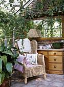 Wintergarten mit Korbsessel, einer Holzkommode mit Schubladen, einem darüber hängenden Spiegel und vielen Zimmerpflanzen