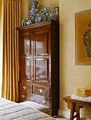 Antiker Kleiderschrank aus Eichenholz in einem traditionellen Schlafzimmer