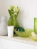 Green glass bowls and a vase of hyacinths on a shelf in the bathroom